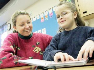 teacher sitting next to student who is reading a braille book