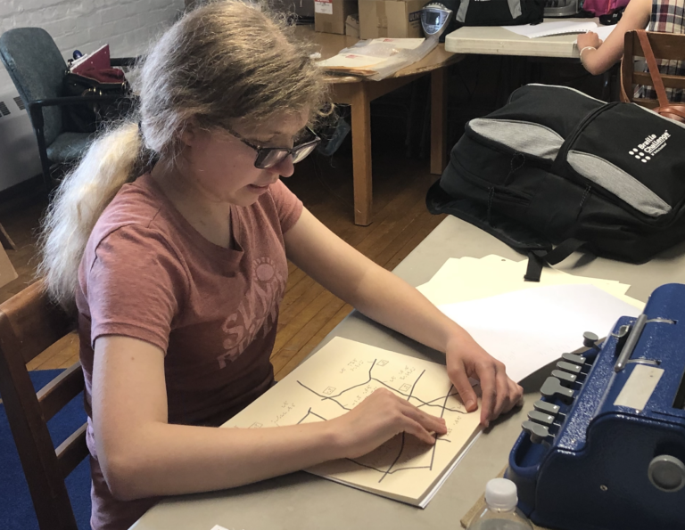 Kaleigh sitting at a table reading a tactile graph during the 2020 NJ Regional Braille Challenge